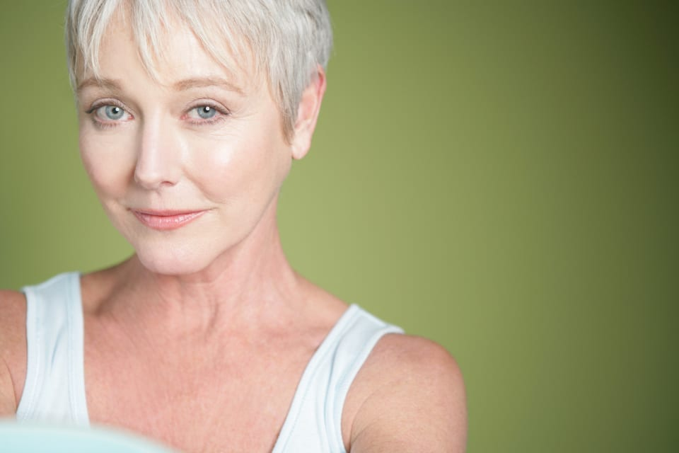 Mature woman with short hair in front of a green solid background.